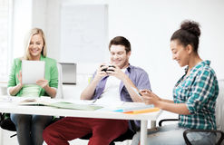 Students looking into devices at school. Education, technology and internet - students looking into phones and tablet pc at school Stock Image