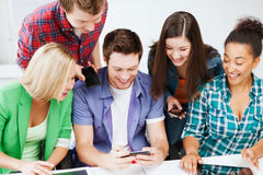 Students looking into smartphone at school. Education concept - group of students looking into smartphone at school Stock Images