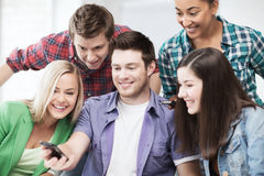 Students looking into smartphone at school Royalty Free Stock Image
