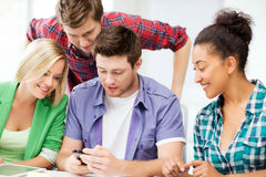 Students looking at smartphone at school Royalty Free Stock Images