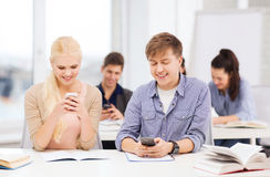 Students looking into smartphone at school Stock Photo
