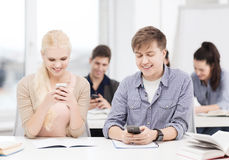 Students looking into smartphone at school Royalty Free Stock Photos