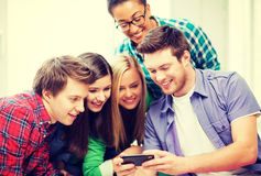 Students looking at smartphone at school. Education and technology - group of students looking at smartphone at school Stock Images