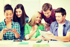 Students looking at smartphones and tablet pc Stock Image