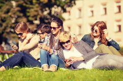 Students looking at smartphones and tablet pc Royalty Free Stock Photography