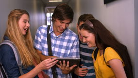 Students looking at tablet pc in the hall at the university stock footage