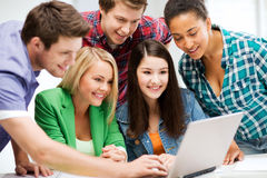 Students looking at tablet pc in lecture at school. Education and internet - smiling students looking at tablet pc in lecture at school Stock Photos