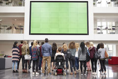 Students looking up at a big screen in university atrium Royalty Free Stock Image