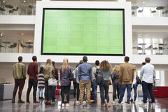 Students looking up at a big screen in university building royalty free stock photography