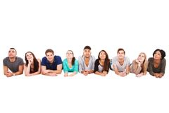 Students lying in a row over white background Stock Photography