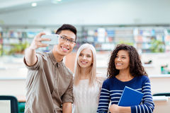 Students making selfie photo on smartphone. Smiling multi ethnic students making selfie photo on smartphone in the university library Stock Photography