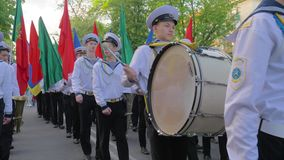 Students of Marine Academy march on a parade with multicolored flags in their hands, a young sailor with sticks close-up. Kherson, Ukraine - May 20, 2019 stock video footage