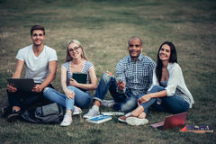 Students near university. Students are sitting on the grass near university. Listening to music, working on laptop. Taking break from studying Royalty Free Stock Photo