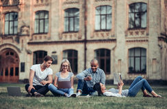 Students near university. Students are sitting on the grass near university. Listening to music, working on laptop. Taking break from studying Stock Photography