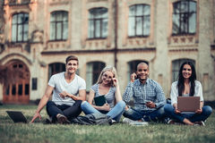 Students near university. Students are sitting on the grass near university. Listening to music, working on laptop. Taking break from studying Stock Photo