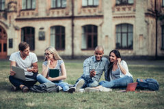 Students near university. Students are sitting on the grass near university. Listening to music, working on laptop. Taking break from studying Royalty Free Stock Images