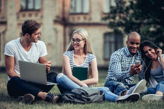 Students near university. Students are sitting on the grass near university. Listening to music, working on laptop. Taking break from studying Stock Images