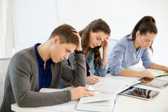 Students with notebooks and tablet pc at school Royalty Free Stock Image