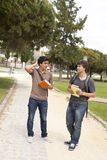 Students outdoor. Two young student talking at the school park Stock Photos