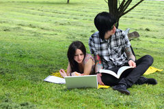 Students outdoor. Couple of students studying outdoor with laptop Royalty Free Stock Image