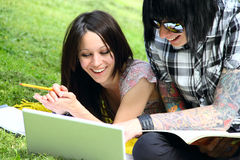 Students outdoor. Couple of students studying outdoor with laptop Stock Image