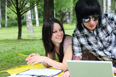 Students outdoor. Couple of students studying outdoor with laptop Royalty Free Stock Photo