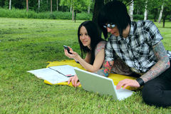 Students outdoor. Couple of students studying outdoor with laptop Stock Photo