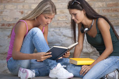 Students outdoors. Happy female students reading outdoors Royalty Free Stock Photos