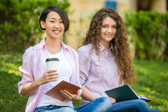 Students outdoors. Female beautiful smiling students studying outdoors on campus at the university Stock Photo