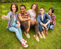 Students outdoors. Group of young attractive smiling students dressed casual making selfie outdoors on campus at the university Royalty Free Stock Photos