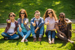 Students outdoors. Group of young attractive smiling students dressed casual sitting on the lawn in park and resting Royalty Free Stock Images