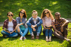Students outdoors. Group of young attractive smiling students dressed casual sitting on the lawn in park and studying Stock Images