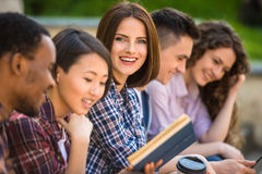 Students outdoors. Group of young attractive smiling students dressed casual sitting on the staircase outdoors on campus at the university Royalty Free Stock Images
