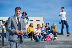 Students outside sitting on steps. Group portrait  of happy  students outside in front of school sitting on steps have fun Stock Images