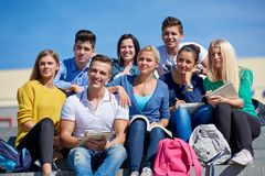 Students outside sitting on steps. Group portrait  of happy  students outside in front of school sitting on steps have fun Royalty Free Stock Photo