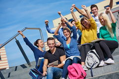 Students outside sitting on steps. Group portrait  of happy  students outside in front of school sitting on steps have fun Stock Photo
