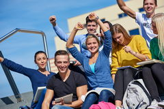 Students outside sitting on steps. Group portrait  of happy  students outside in front of school sitting on steps have fun Stock Image