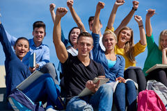 Students outside sitting on steps. Group portrait  of happy  students outside in front of school sitting on steps have fun Royalty Free Stock Image