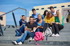 Students outside sitting on steps. Group portrait  of happy  students outside in front of school sitting on steps have fun Royalty Free Stock Photography