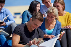 Students outside sitting on steps. Group portrait  of happy  students outside in front of school sitting on steps have fun Stock Photos