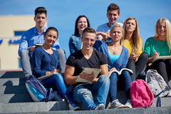 Students outside sitting on steps. Group portrait  of happy  students outside in front of school sitting on steps have fun Royalty Free Stock Images