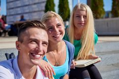 Students outside sitting on steps Stock Photo