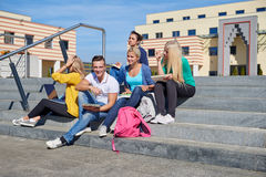 Students outside sitting on steps. Group portrait  of happy  students outside sitting on steps have fun Royalty Free Stock Photos