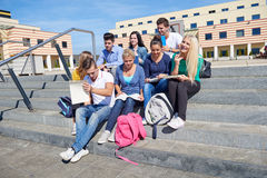 Students outside sitting on steps. Group portrait  of happy  students outside sitting on steps have fun Stock Photography
