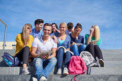 Students outside sitting on steps. Group portrait  of happy  students outside sitting on steps have fun Royalty Free Stock Image