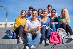 Students outside sitting on steps. Group portrait  of happy  students outside sitting on steps have fun Stock Images