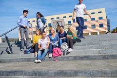 Students outside sitting on steps. Group portrait  of happy  students outside sitting on steps have fun Stock Photos