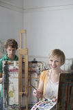 Students Painting At Easels In Art Class stock photography