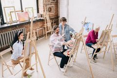 Students Painting at Easels in Art Studio royalty free stock photography
