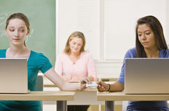 Students passing notes in classroom Royalty Free Stock Photos